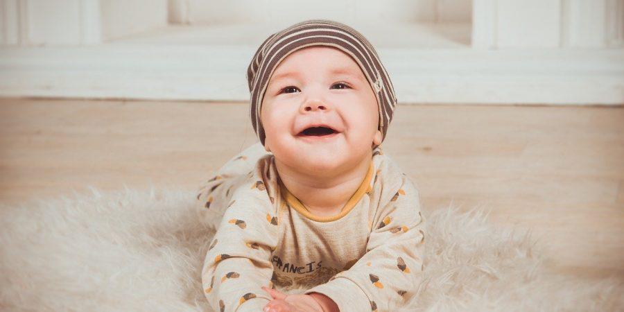 bébé qui sourit en étant allongé sur le sol